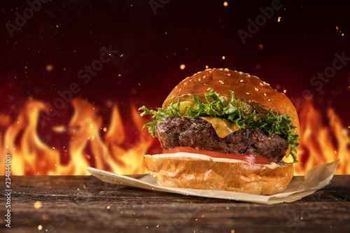 Delicious hamburger with fire on background
