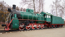 Side View Of Classic Old Green Steam Locomotive On Rail Tracks