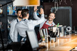 canvas print picture - handsome smiling barmen in aprons high five at workplace