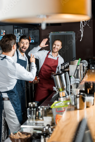 cheerful barmen in aprons high five at workplace