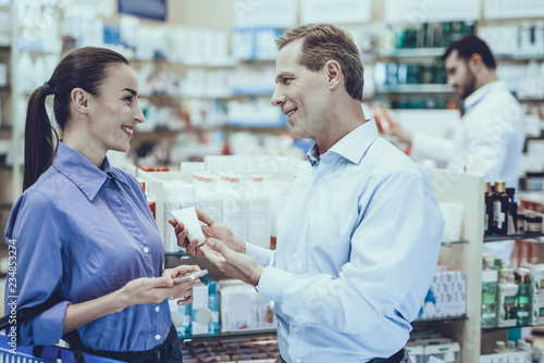 Photo  Man and woman buys a medicaments in pharmacy
