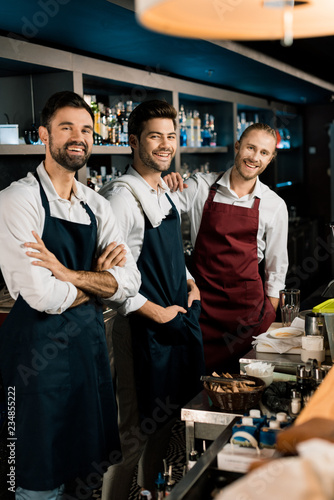 Fototapeta Handsome bartenders standing in aprons and smiling in bar obraz