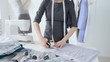 Concept of hobby and small business. Young female seamstress designs and sews clothes