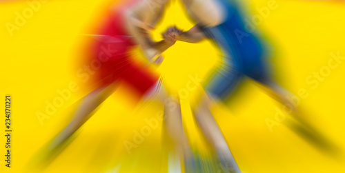 Fotografie, Obraz  Two wrestling fighting on yellow background. Zoom blur.