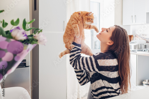 Young woman playing with cat in kitchen at home Fototapet