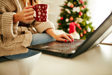 Woman Holding Cup Of Coffee While Working On Laptop At Home For Christmas. New Year And Xmas Concept.