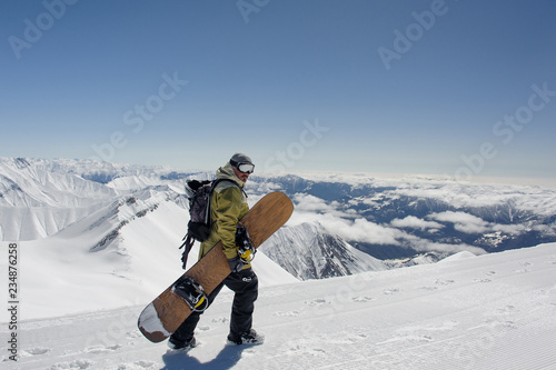 Side view manful snowboarder walking with the snowboard in the mountain resort