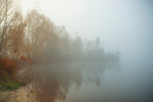 Misty Morning On The Lake. Gazebo Or Hunting Lodge In The Forest By The Lake. Trees And Grass Near Water. Calm Autumn Landscape.