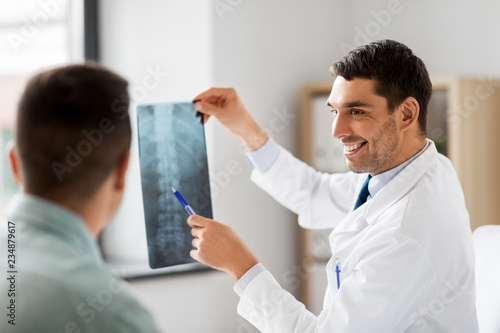 Fotografía medicine, healthcare and people concept - smiling doctor showing x-ray to patien