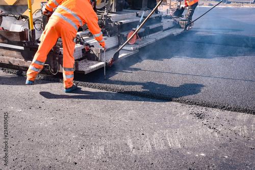 Fotografiet Straßenbau - neue Asphaltdecke wird gezogen, Arbeiter misst die Schichtdicke