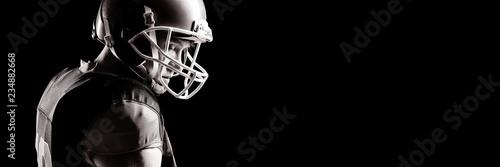 Obraz na plátně American football player in helmet standing against black