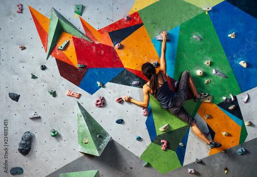 Fototapeta girl is climbing on the wall in the training room obraz