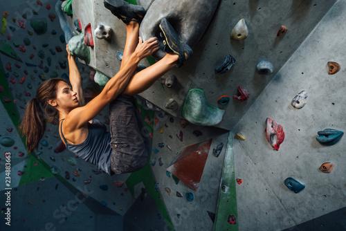 Fototapeta the girl hangs on the ledges climbing the wall in training room