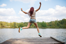 Photo From Back Of Young Jumping Woman On Wooden Bridge By River