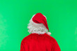 Leinwandbild Motiv Merry Christmas. Santa Claus in a red suit is standing with his back and is looking forward on a green screen background chroma key