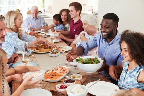 Keuken foto achterwand Kruidenierswinkel Group Of Multi-Generation Family And Friends Sitting Around Table And Enjoying Meal