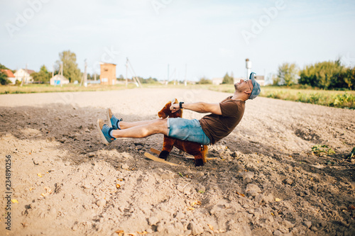 Adult stylish man riding wooden toy horse on field outdoor Fotobehang