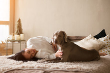 Happy Young Woman In A Pajamas With Dog Weimaraner Sits On A Bed At Home. Winter Or Christmas Weekend Concept.