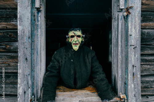 Fotografía  Unknown person with creepy horrible latex mask looking out from old wooden ghost house window