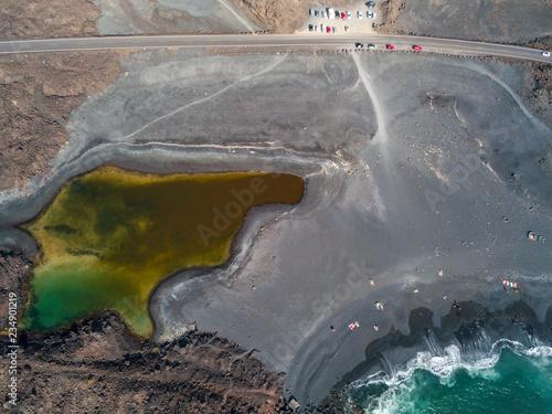 Vista aerea del piccolo lago sotto la montagna Bermeja, vista della spiaggia nera e della strada costiera. Lanzarote, Isole Canarie, Spagna