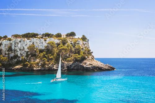 Beautiful bay with sailing boat yacht, Cala Galdana, Menorca island, Spain. Yachting, travel and active lifestyle concept