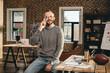 casual businessman talking on smartphone in loft office
