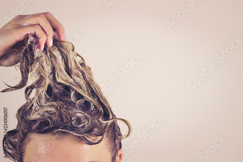 Obraz Funny woman pulls himself wet hair up. Close-up, space for text. Hair care concept - fototapety do salonu