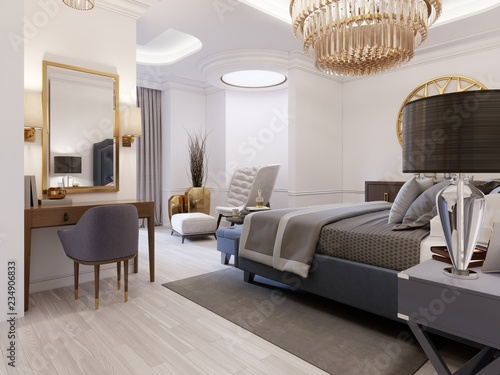 The design of a luxurious bedroom in a contemporary style with a blue bed and white walls. Armchair with footrest and dressing table with mirror.