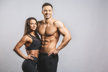 Fototapeta Athletic man and woman isolated over white background. Personal fitness instructor. Personal training.