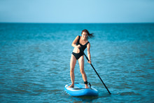 Happy Beautiful Young Girl With Paddle Board On A Tropical Beach. Blue Sea In The Background. Summer, Vacation, Sup Paddleboarding Or Surfing, Travel, Lifestyle Concept.