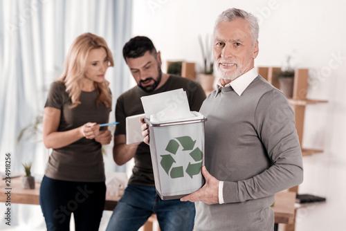 Valokuva  Happy aged man holding a litter bin