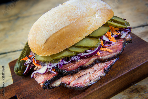 Detail of Brisket Sandwich with cucumber and coleslow on cutting board