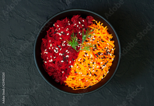 Raw vegan salad with fresh beetroot and carrot flavored with olive oil and sesame seeds on dark concrete background Tapéta, Fotótapéta