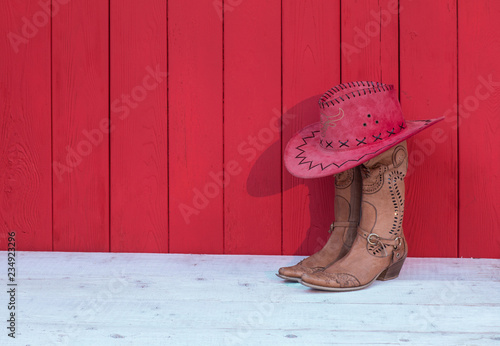 Fényképezés Cowboy women's boots, hat on a red wooden background