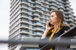canvas print picture Young business woman uses cellphone at the street