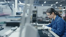 Time Lapse Of Young And Senior Electronics Factory Workers In Blue And White Work Coats Using Pliers And Tweezers To Assemble Printed Circuit Boards For Smartphones. High Tech Factory Facility.