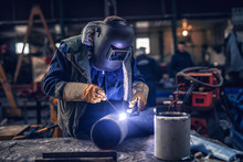 Worker Welding Iron. Protective Suit And Mask On. Workshop Interior.
