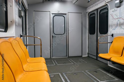 Fotografía  Kyiv metro wagon interior with no people and orange seats