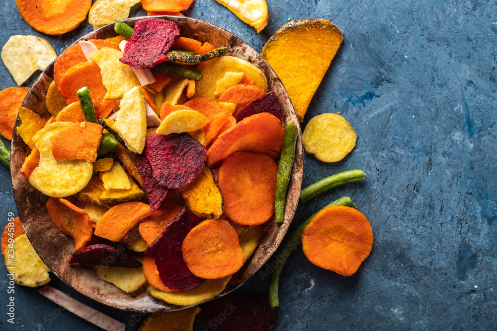 Fototapeta Dried vegetables chips from carrot, beet, parsnip and other vegetables on blue backgrounds. Organic diet and vegan food