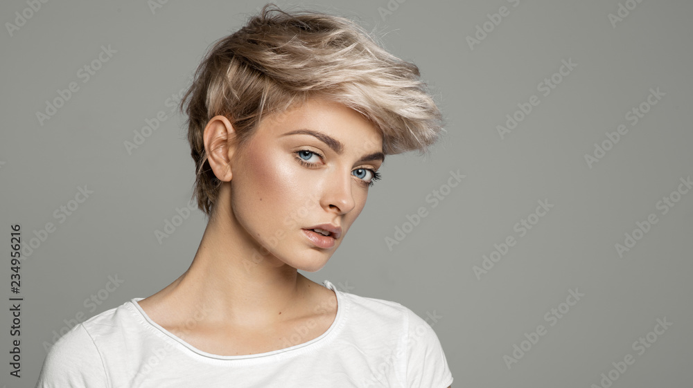 Fototapety, obrazy: Portrait of young girl with blond short hairstyle looking at camera isolated on gray background with copy space