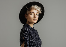 Fashion Portrait Of Female Model With Blond Short Hair Wear Black Hat And Looking At Camera