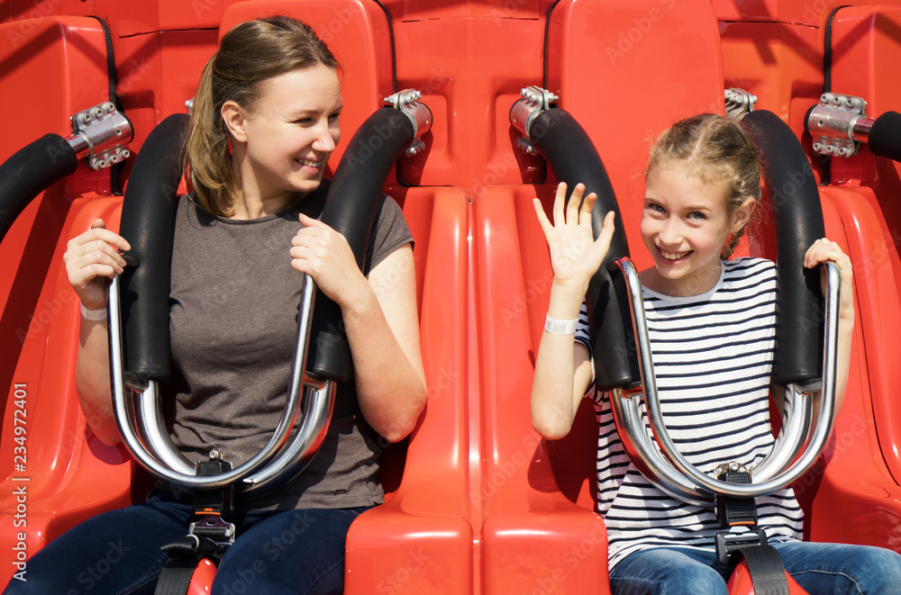 Fototapeta Mom and daughter are sitting on the attraction in the park.