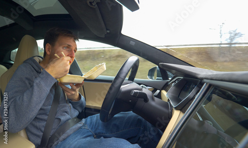 Vászonkép  CLOSE UP: Young man eating Chinese food while driving in his high tech car