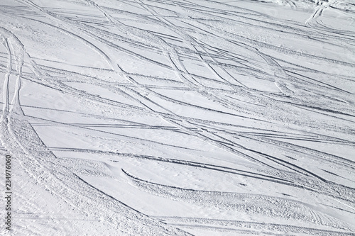 Groomed snowy ski slope with trace from skis and snowboards