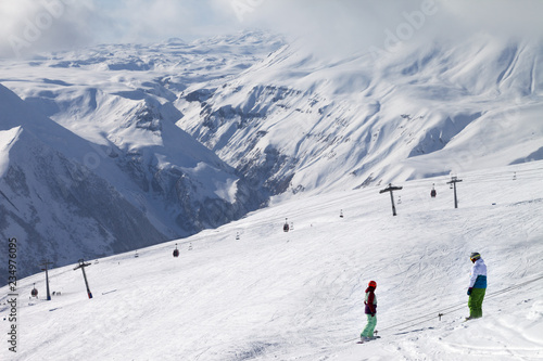 Two snowboarders descend on snowy ski slope