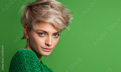 Fotografie, Obraz  Portrait of young woman with blond short hair isoalted on green background