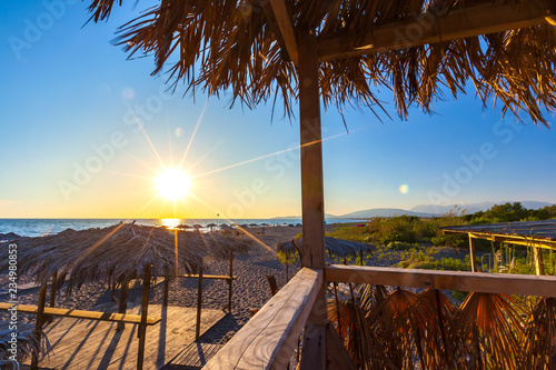 Sunset with colorful sun rays on the shore of the Adriatic Sea, paths sunbeds and umbrellas made of wood and straw in the recreation area on the sand Wallpaper Mural