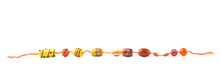 Line Of Threading Glass Beads Isolated On White Background. Orange  Decorated Jewelry Glass Beads.