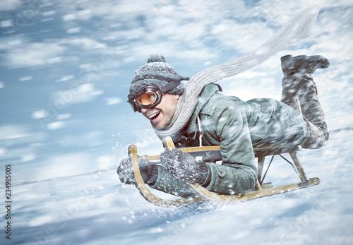 Obraz Mann in voller Fahrt beim Rodeln im Schnee - fototapety do salonu
