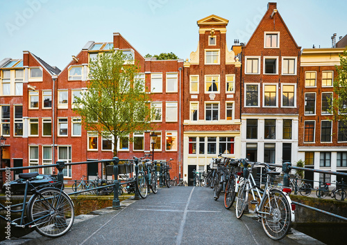 Amsterdam, Netherlands. Bridge with bicycles along road on water Wallpaper Mural